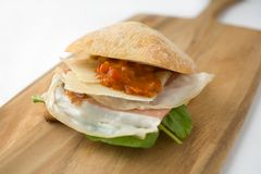 Ham and cheese sandwich. With prosciuto ham, parmesan cheese, roasted red peppers, arugula, on fresh chabitta bread Stock Photo