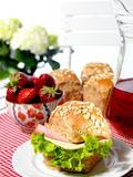 Ham and cheese sandwich. Plate with ham and cheese sandwich on red-chequered tablecloth. In the background flower, strawberries in the bowl and pitcher with Royalty Free Stock Images