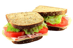 Ham and Cheese Sandwich on Whole Grains Bread. Sandwich made from Slices of Whole Grains Bread, Ham and Cheese garnished with organic fresh Sliced Tomatoes and Stock Images