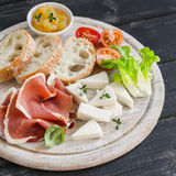 Ham, cheese, tomatoes and ciabatta bread served on a light wooden board on a dark wooden surface. Tasty Breakfast, snack or delicious appetizer to wine stock photos