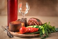 Ham, cheese, vegetables and red wine on craft background. Still life with food and drink. Ham, cheese, vegetables and red wine on craft background royalty free stock image