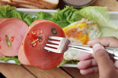 Ham cut into circular discs with red peppers and egg fried. Royalty Free Stock Photography