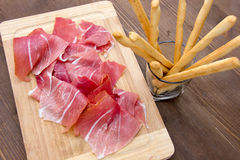 Ham on cutting board with bread sticks from above Stock Photos
