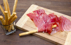Ham on cutting board with bread sticks Stock Image