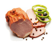Ham decorated with green Bulgarian pepper. Over white background Royalty Free Stock Image