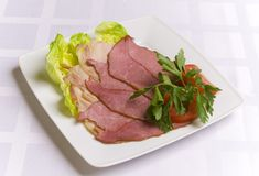 Ham decorated with salad, tomato and parsley stock photography