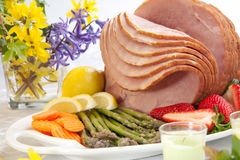 Ham For Easter. Festive glazed ham for Easter celebration dinner garnished with asparagus, carrots, strawberry, and lemon wedges Stock Images