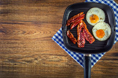 Ham and Egg. Bacon and Egg. Salted egg and sprinkled with black pepper.  Grilled bacon, two eggs in a Teflon pan. Ham and Egg. Bacon and Egg. Salted egg and Stock Image