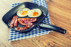 Ham and Egg. Bacon and Egg. Salted egg and sprinkled with black pepper. Grilled bacon, two eggs in a Teflon pan Royalty Free Stock Photos