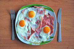 Ham and eggs. On a plate with knife and fork Stock Photo