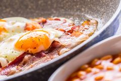 Ham and Eggs. Bacon and Eggs frying on ceramic pan. Salted egg and sprinkled with red pepper. English breakfast.  Royalty Free Stock Photo
