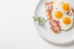 Ham and Eggs. Bacon and Eggs. Salted egg with pepper on white pl. Ate. English breakfast Royalty Free Stock Image