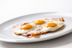 Ham and Eggs. Bacon and Eggs. Salted egg with pepper on white pl Stock Photography