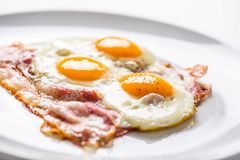 Ham and Eggs. Bacon and Eggs. Salted egg with pepper on white pl. Ate. English breakfast Royalty Free Stock Photos