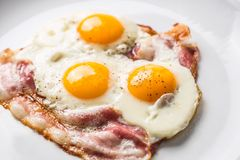 Ham and Eggs. Bacon and Eggs. Salted egg with pepper on white pl Stock Photos