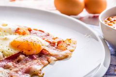 Ham and Eggs. Bacon and Eggs. Salted egg and sprinkled with red pepper. English breakfast.  Royalty Free Stock Photo