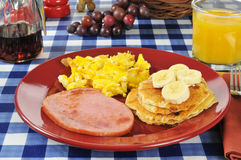 Ham and eggs with pancakes. Grilled ham iwth scrambled eggs and pancakes on a picnic table Stock Image