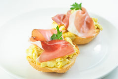 Ham and eggs sandwich. Ham and scrambled eggs sandwich on a plate Stock Image