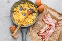 Ham and eggs. Scrambled eggs with bacon in ceramic pan.  Royalty Free Stock Photos