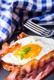 Ham en Ei Bacon en Ei Gezouten ei en bestrooid met zwarte peper en groene kruiddecoratie Royalty-vrije Stock Foto