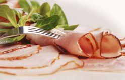 Ham and fork. A close up of decorated ham plate with fork on top Royalty Free Stock Images