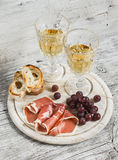 Ham, grapes, ciabatta bread and two glasses with white wine Stock Image