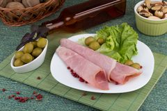 Ham with green olives and salad served on a plate. Ham with green olives and salad and pepper served on a plate Royalty Free Stock Photos
