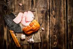 Ham with a hatchet and garlic on the Board. On wooden background Stock Image