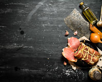 Ham with a hatchet and spices . On the black chalkboard Stock Image