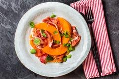 Ham jamon, melon and arugula salad on grey plate Stock Images