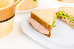 Ham and lettuce sandwich on a white plate Stock Photos