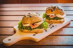 Ham and lettuce sandwiches. On a wooden plate and table Stock Photography