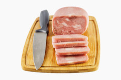 Ham lying on a cutting Board with a knife. Ham on a cutting Board with a knife isolated background Stock Photo