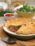 Ham and meat pie. With homemade ketchup and green salad with serving spatula on side and decorations in the background royalty free stock photo