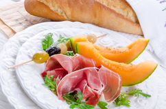 Ham with melon and olives Stock Photos