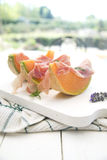 Ham and melon. Presentation of some slices of melon with ham on white-border Stock Photo