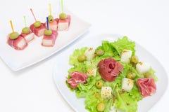 Ham met een meloen en olijven op een witte plaat Royalty-vrije Stock Fotografie