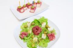 Ham met een meloen en olijven op een witte plaat Royalty-vrije Stock Afbeelding