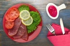 Ham met salade, tomaat en citroen op een plaat Royalty-vrije Stock Afbeeldingen