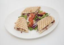 Ham, mushroom and cheese panini. Ham, mushroom and cheese grilled panini with green salad on white china plate Stock Photo