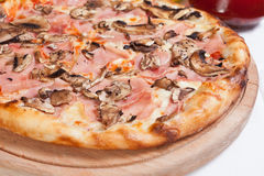 Ham and Mushroom Pizza on a wood plate Royalty Free Stock Image