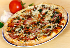 Ham, mushroom and vegetable pizza and tomato at th Royalty Free Stock Images