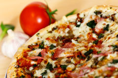 Ham, mushroom and vegetable pizza and tomato at th Royalty Free Stock Image
