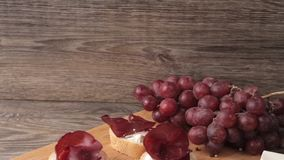 Ham, nuts, crackers and grape on white wooden background stock video
