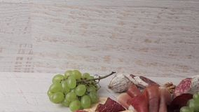 Ham, nuts, crackers and grape on white wooden background stock video footage