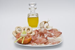 Ham and olive oil. Plate with slices of ham, half a tomato, bread sticks and olive oil Stock Image