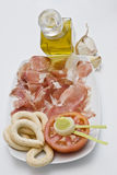 Ham and olive oil with garlics. Plate with slices of ham, half a tomato, bread sticks and olive oil Stock Images