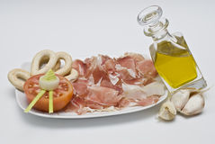 Ham and olive oil and tomato. Plate with slices of ham, half a tomato, bread sticks and olive oil Royalty Free Stock Photography