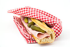 Ham and Pickle Sandwich. Ham and pickles on a french roll wrapped in a red checkered napkin, isolated Royalty Free Stock Image