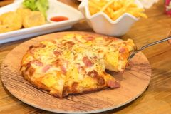 Pizza put on wooden plate. Ham and pineapple pizza on a cutting board detail. pizza put on wooden plate, eating hawaiian pizza Stock Image